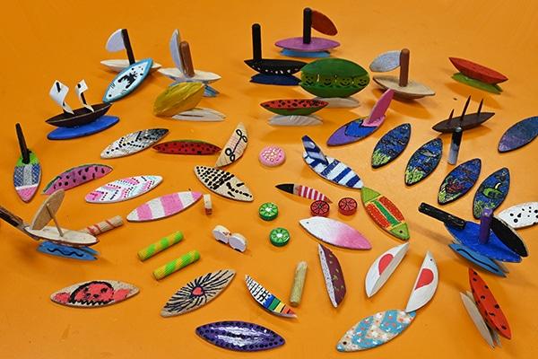 Dřevěné šperky a lodě malované akrylovými barvami.